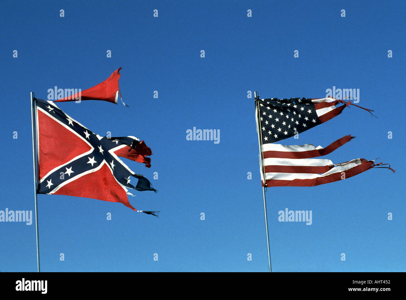 tattered and torn american flag flies along side a southern stock