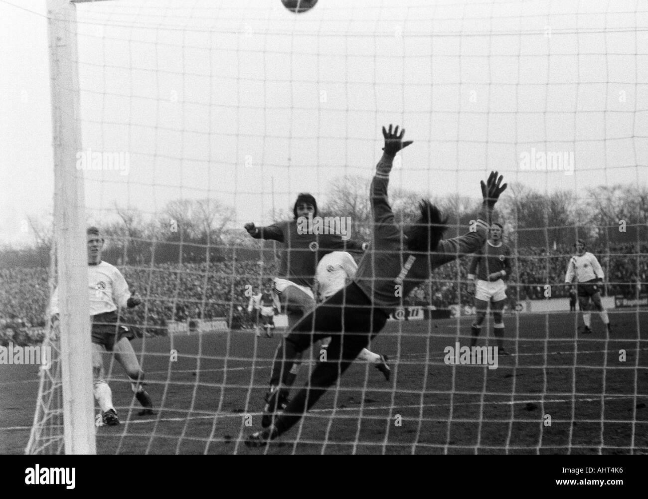 football, Bundesliga, 1970/1971, Niederrhein Stadium, Rot-Weiss Oberhausen versus Rot-Weiss Essen 0:0, scene of the match, f.l.t.r. Heinz Stauvermann (RWE), Hans Fritsche (RWO) shots on goal, keeper Fred Werner Bockholt (RWE), Lothar Kobluhn (RWO) - Stock Image