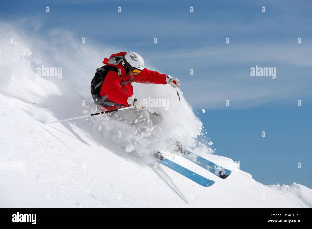 Austria, Saalbach, man skiing on slope sending up snow spray - Stock Image