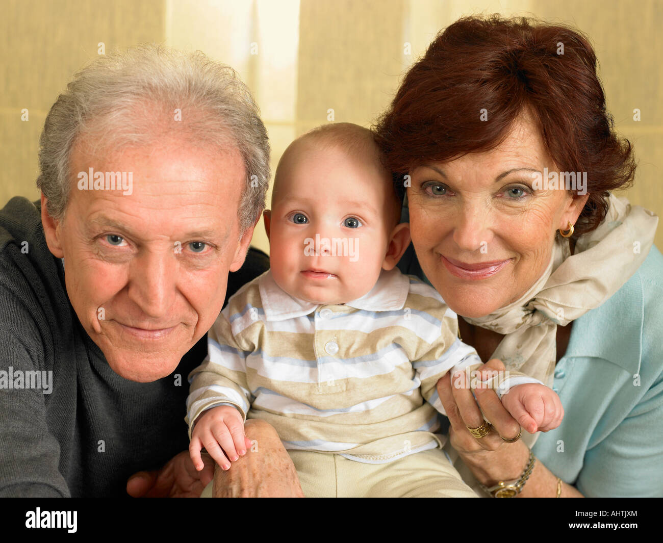 Senior grandparents with baby grandson (1-3 months) smiling, portrait - Stock Image