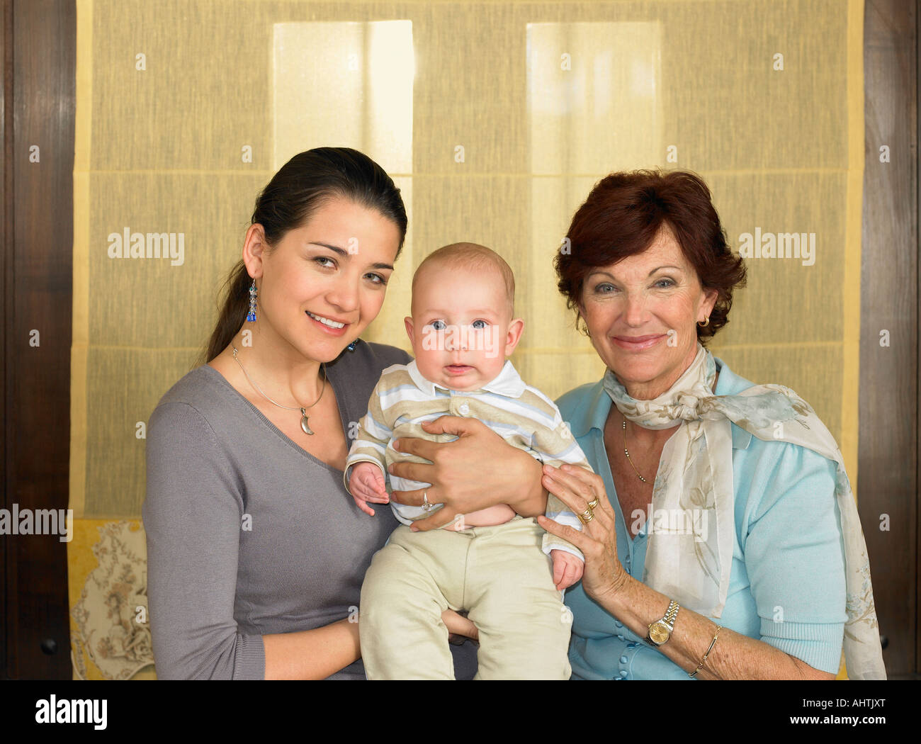 Mother and grandmother holding baby boy (1-3 months) smiling, portrait - Stock Image