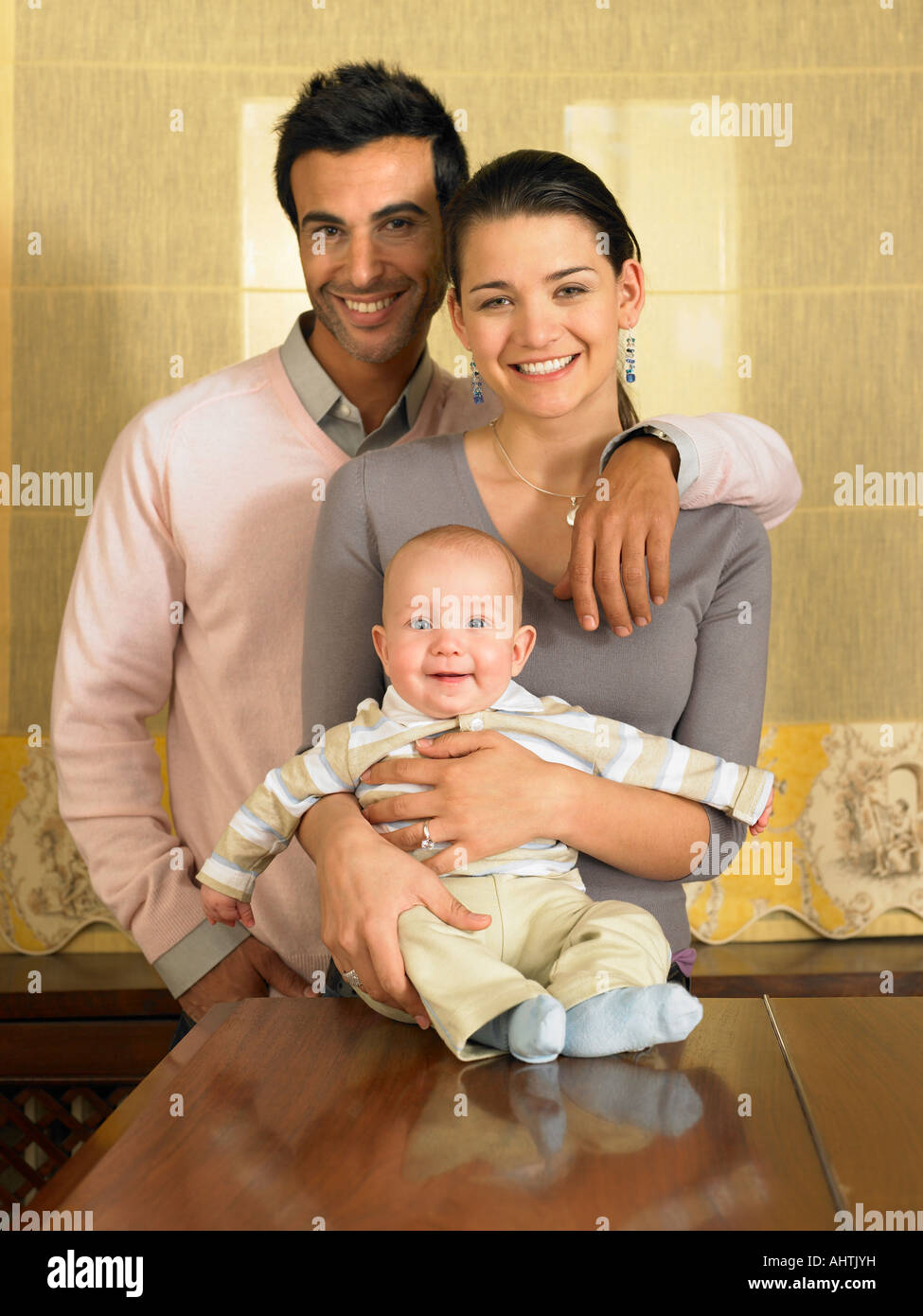 Young couple and baby son (1-3 months) smiling, portrait - Stock Image
