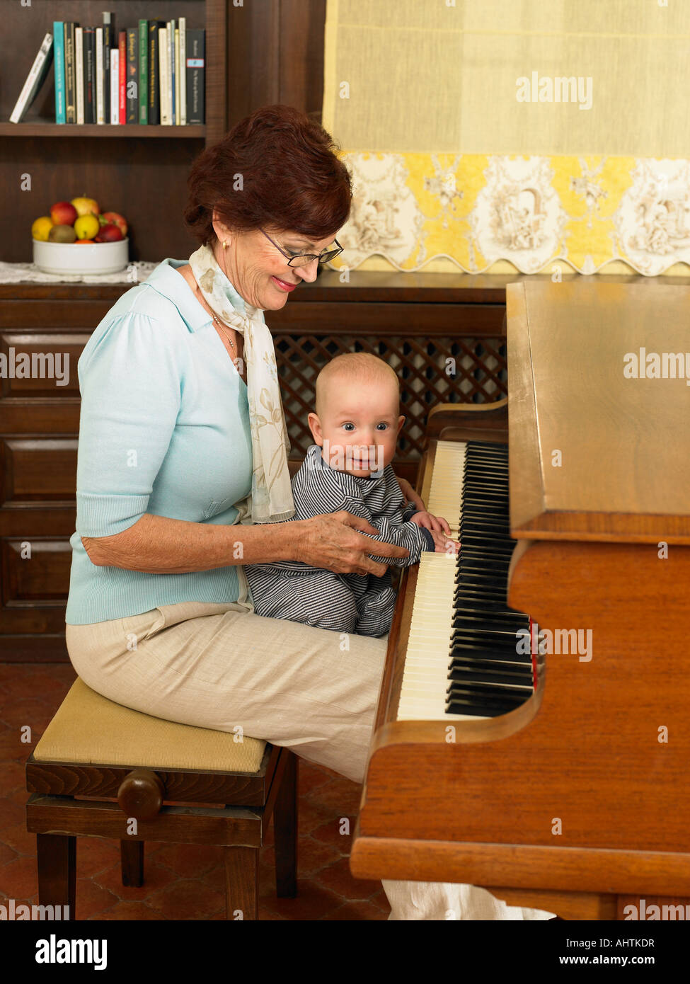 Senior grandmother playing piano with baby grandson (1-3 months) - Stock Image