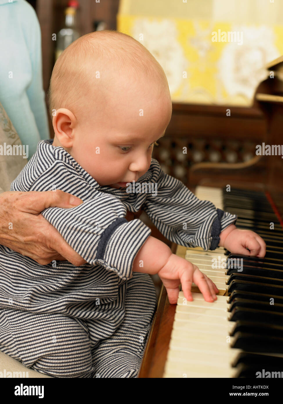 Senior grandmother holding baby grandson (1-3 months) pressing piano keys - Stock Image