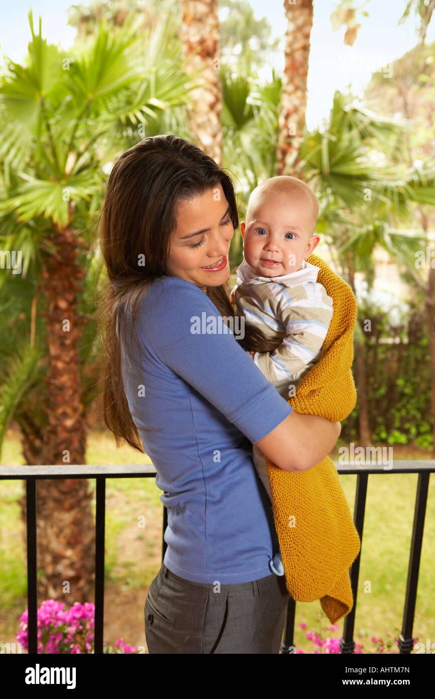 Young mother holding baby son (1-3 months) on balcony, smiling - Stock Image