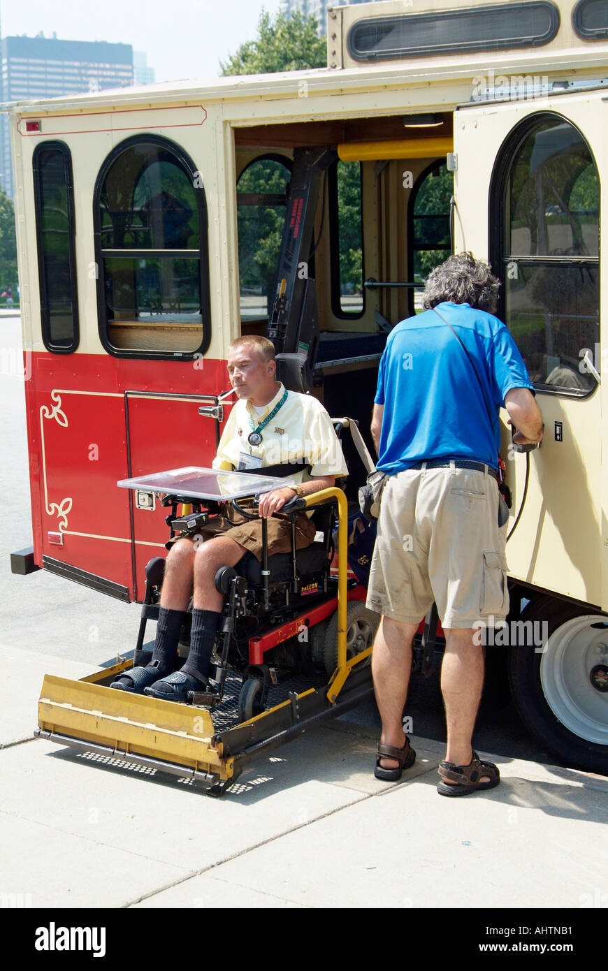Handicapped male in a wheel chair boards a special needs bus at the ...