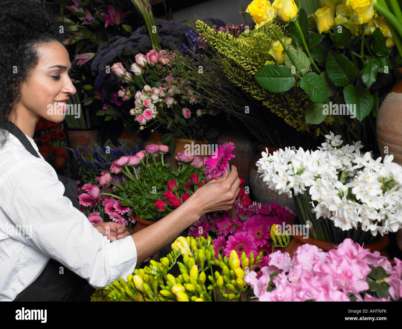 Young female florist selecting flower, smiling, profile Stock Photo