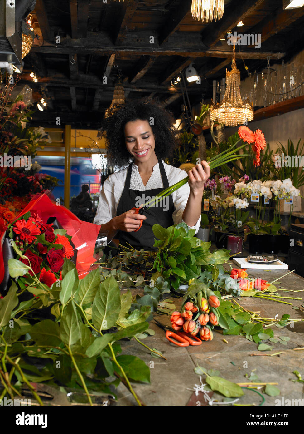 Young female florist trimming flower stems in shop, smiling Stock Photo