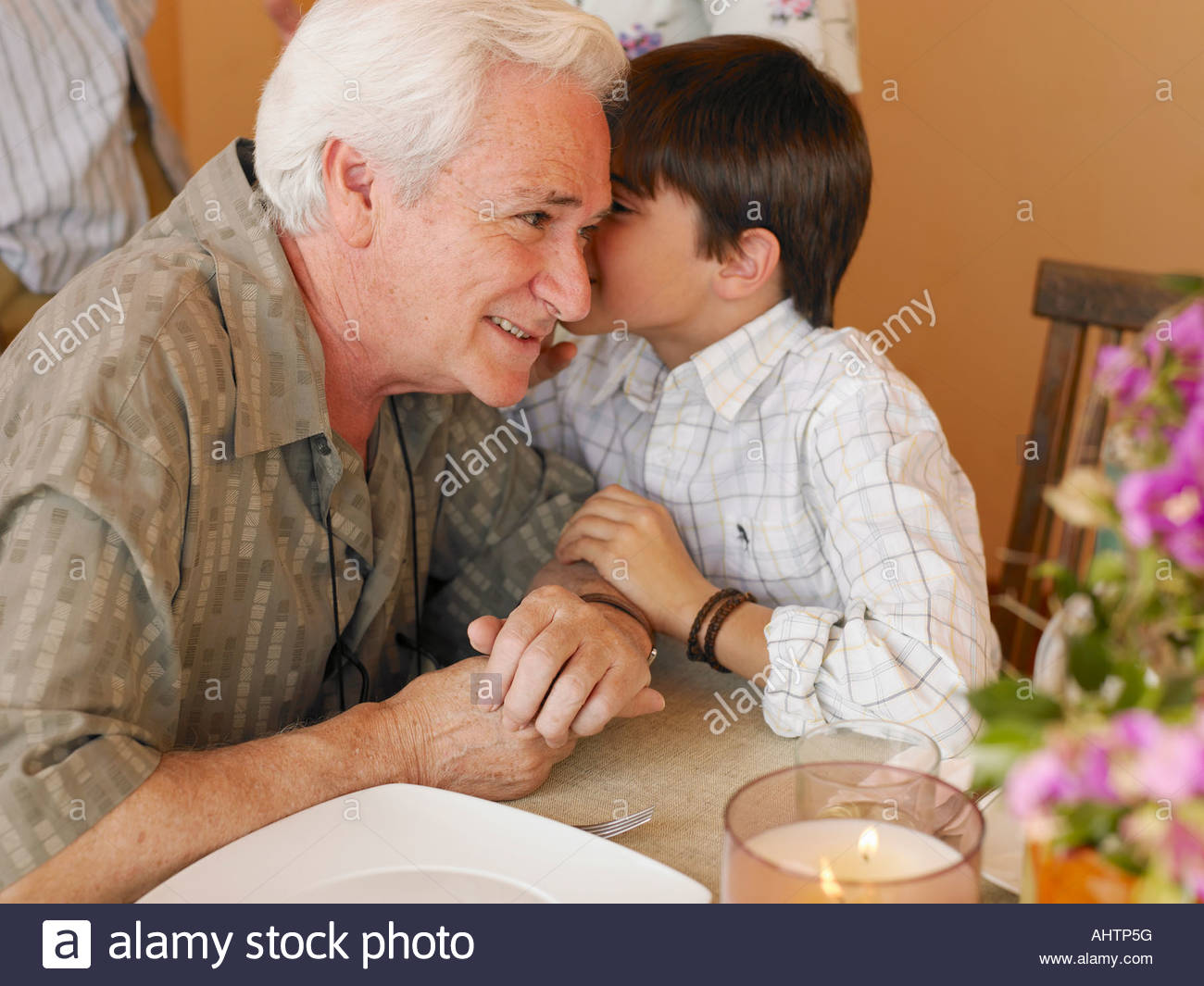 Boy (8-10) whispering in grandfather's ear at dining table Stock Photo