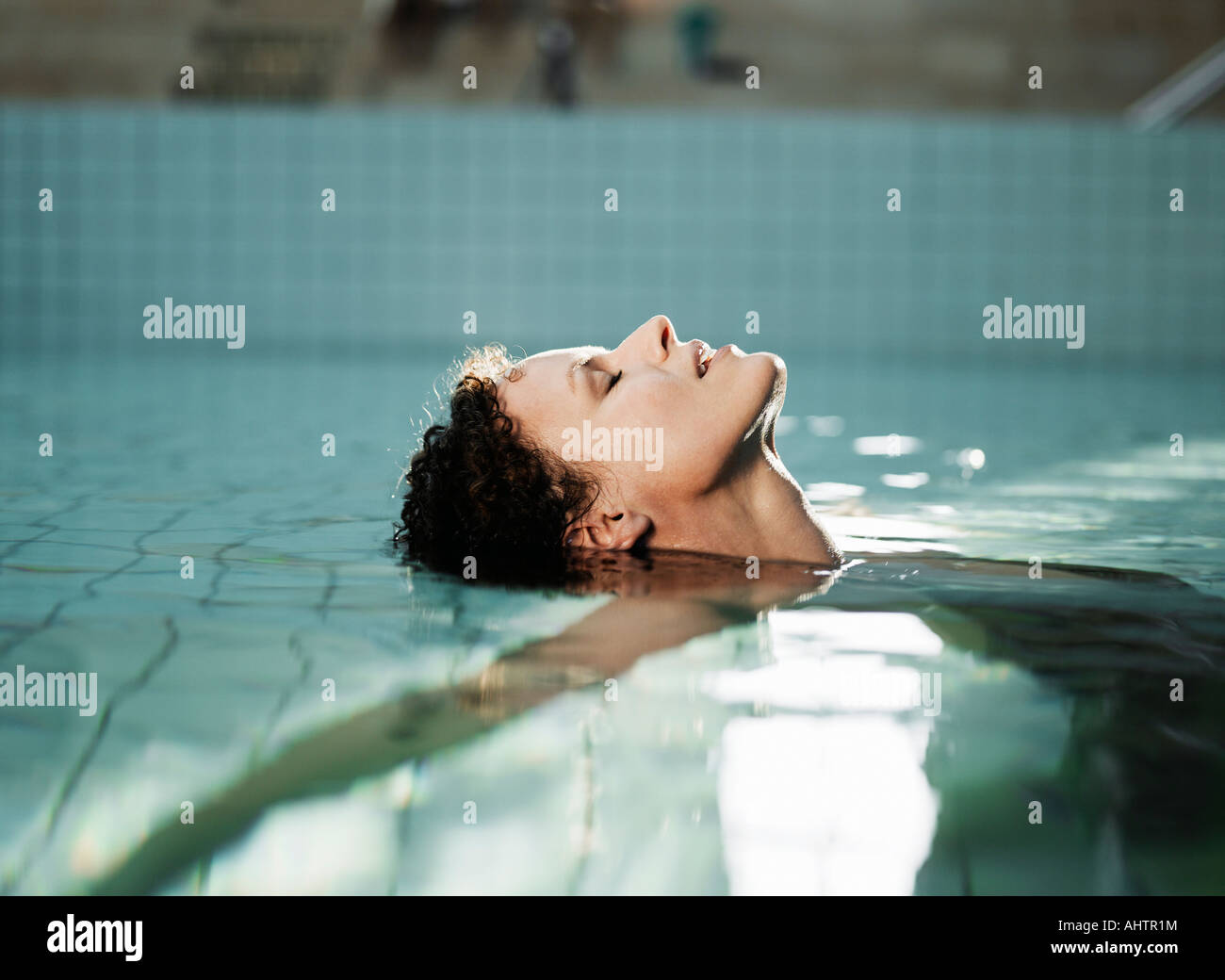 Woman lying in water, side view - Stock Image
