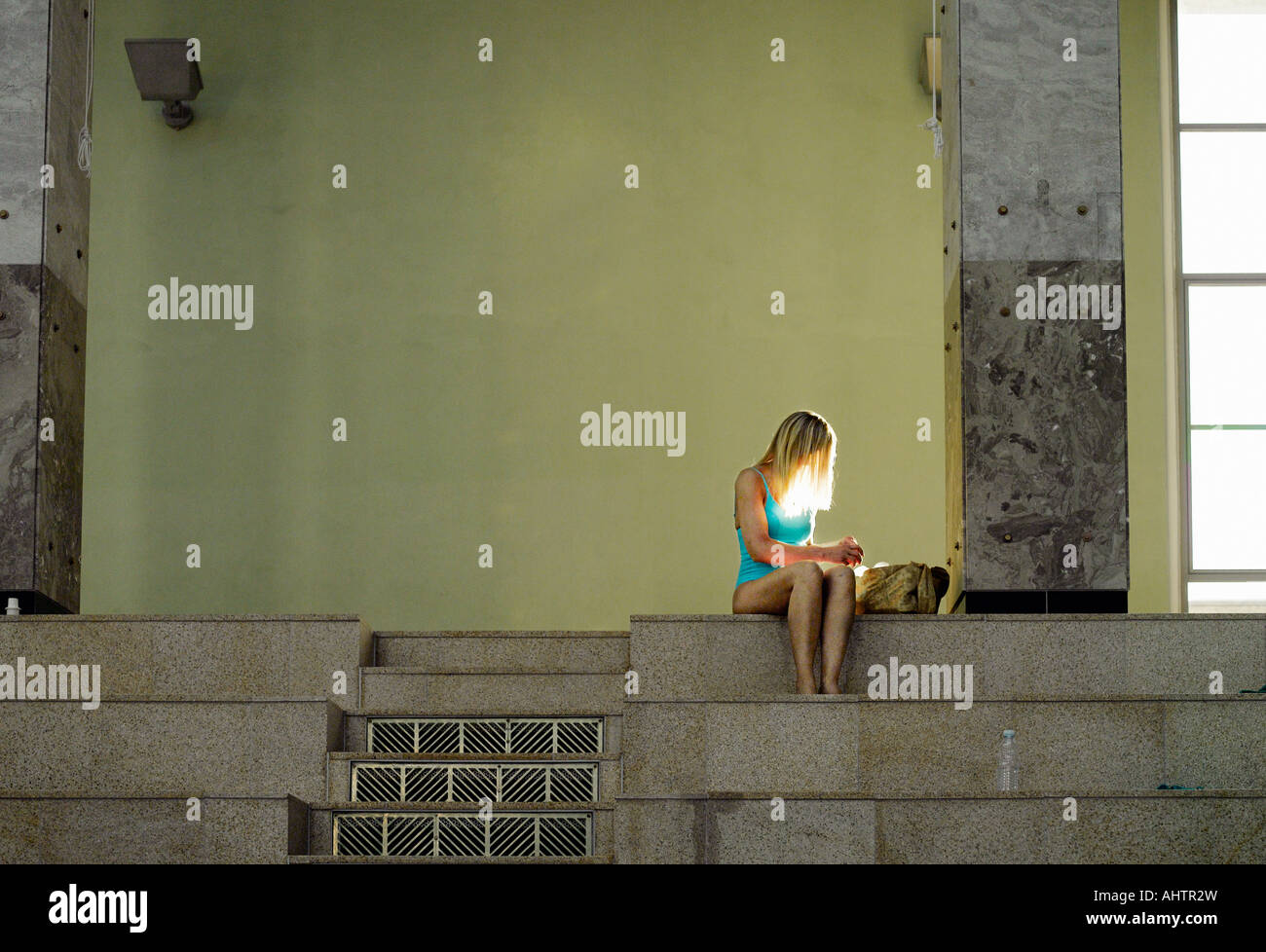 Woman sitting on steps, looking in bag - Stock Image