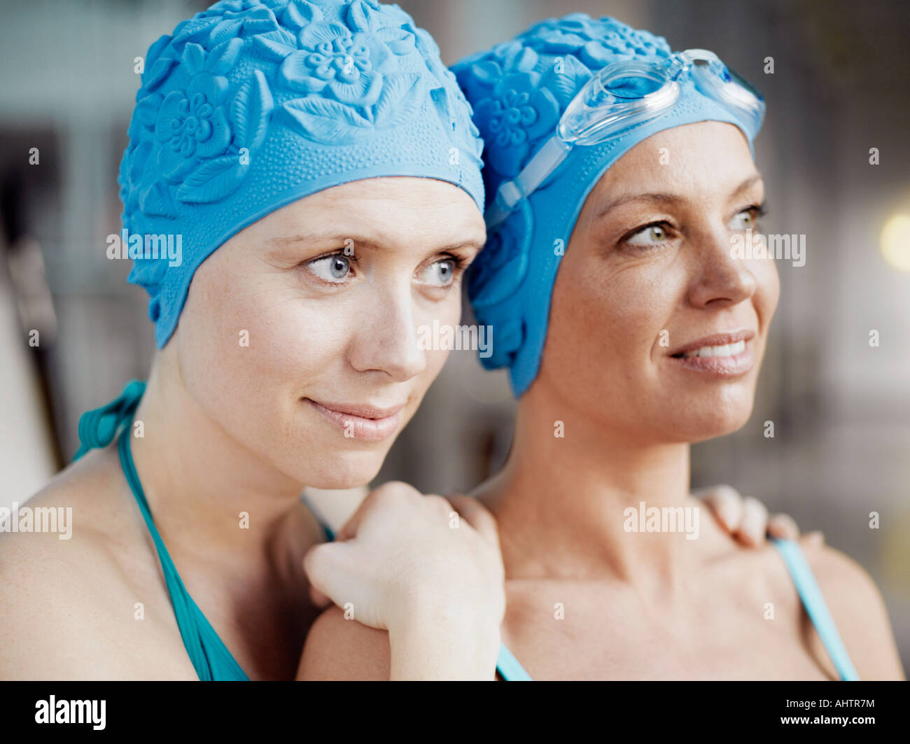 Two women wearing swimming caps and bathing suits efcb1d066