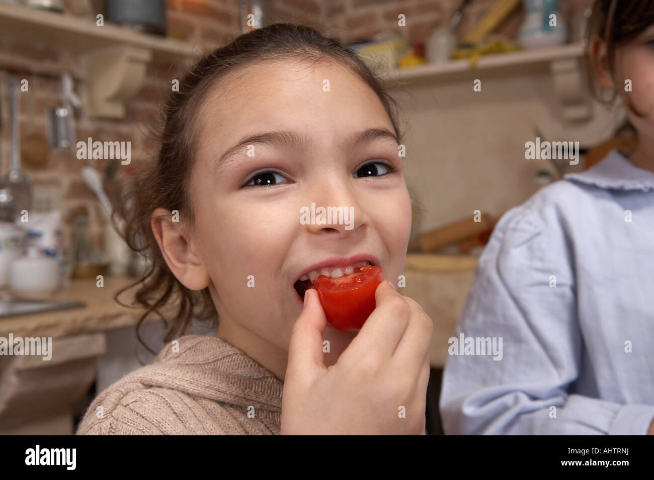 Girl (5-7) eating tomato, close-up, portrait Stock Photo
