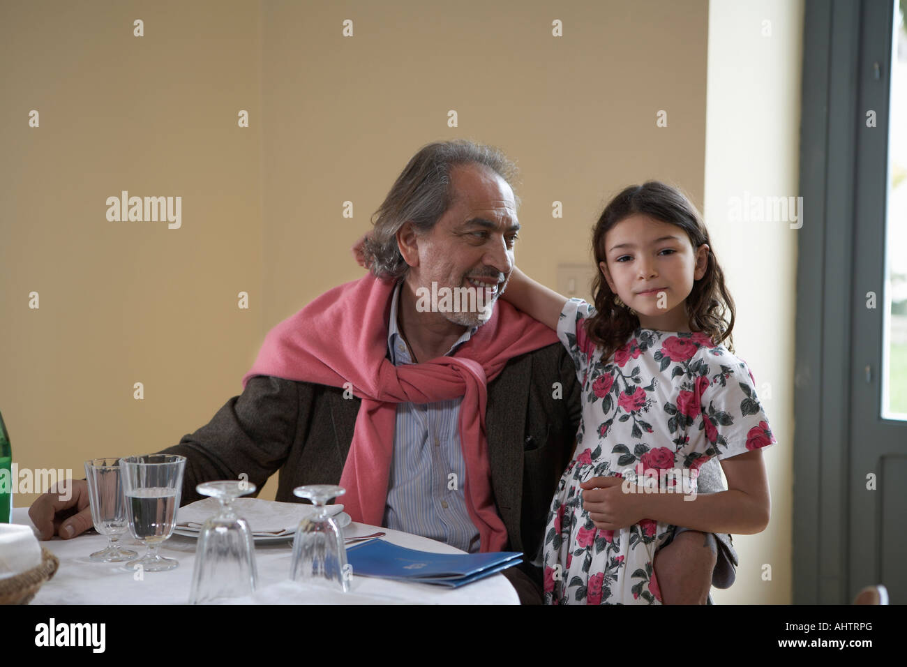 Girl (5-7) sitting with grandfather at a table Stock Photo