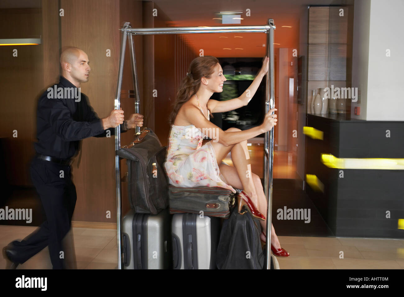 Bellboy pushing woman on luggage trolley - Stock Image