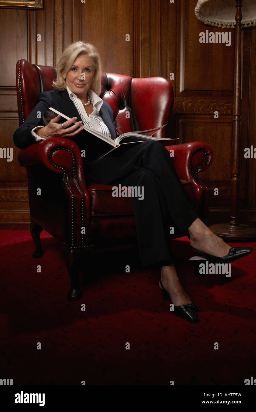 Businesswoman in a comfy leather chair with a book - Stock Image