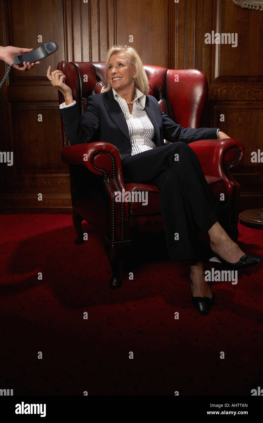 Businesswoman in a comfy leather chair with a phone - Stock Image