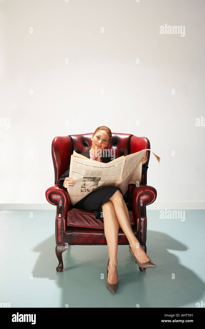 Businesswoman in a comfy leather chair with newspaper - Stock Image