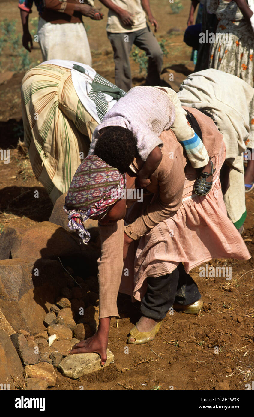 Woman working in the field with her baby on her back. Ethiopia - Stock Image