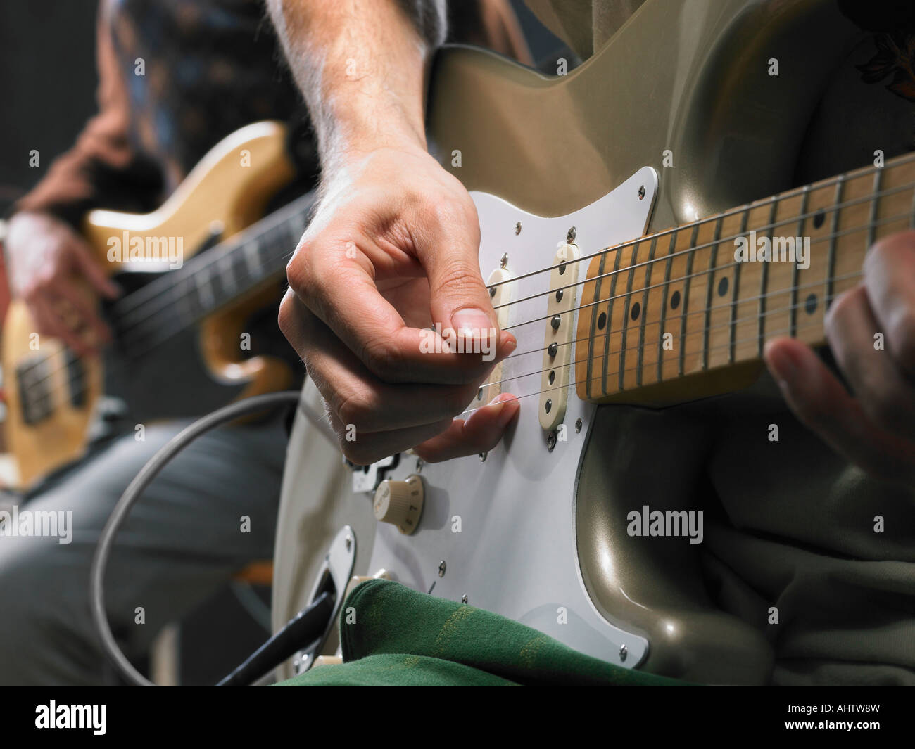 Two electric guitar players close up on hands. - Stock Image