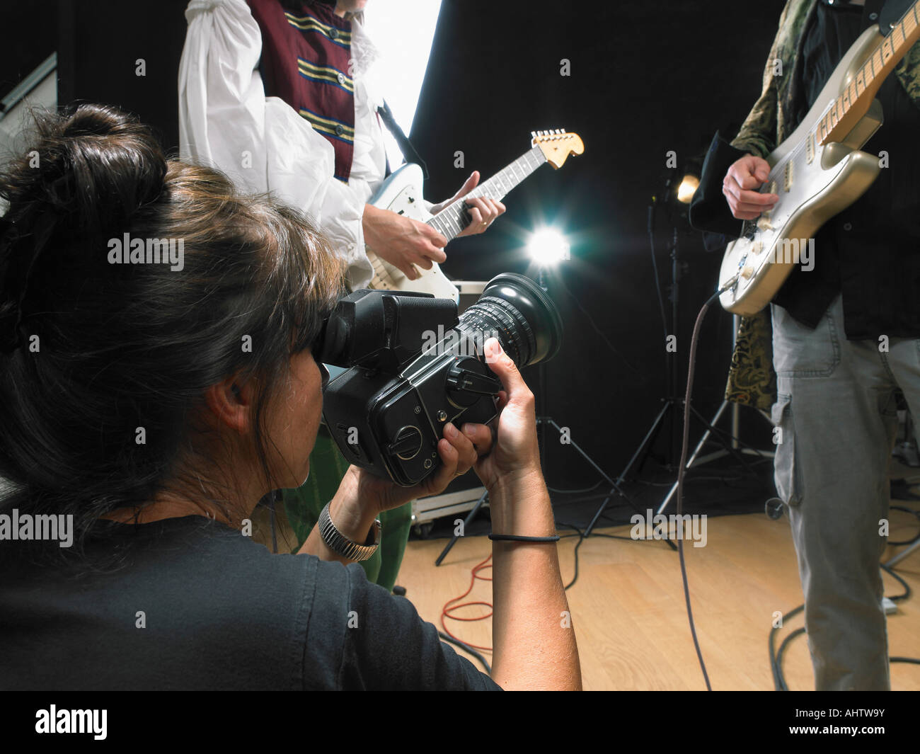 Female photographer shooting two electric guitar players in studio close up. - Stock Image