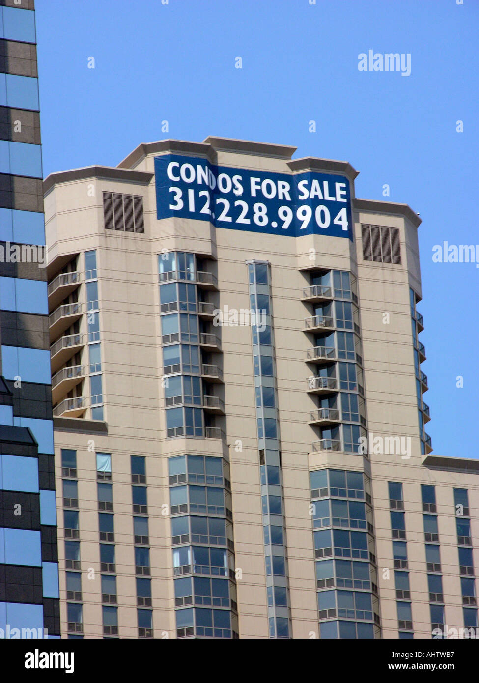 Sign on high rise condo building offering condominiums for sale in downtown Chicago Illinois - Stock Image