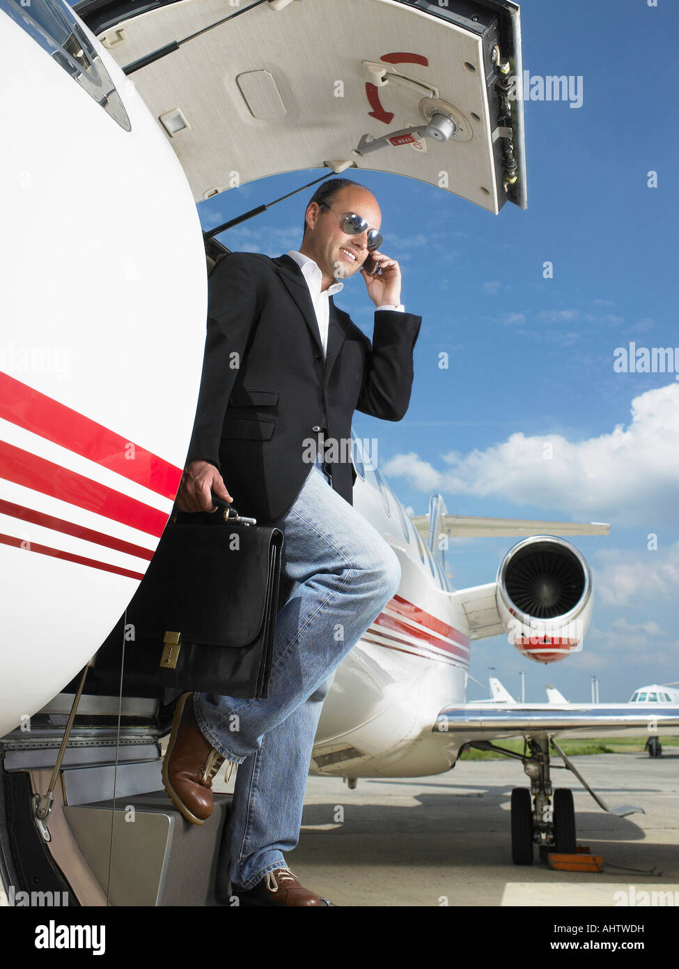 Casual businessman exiting private plane while on phone. - Stock Image