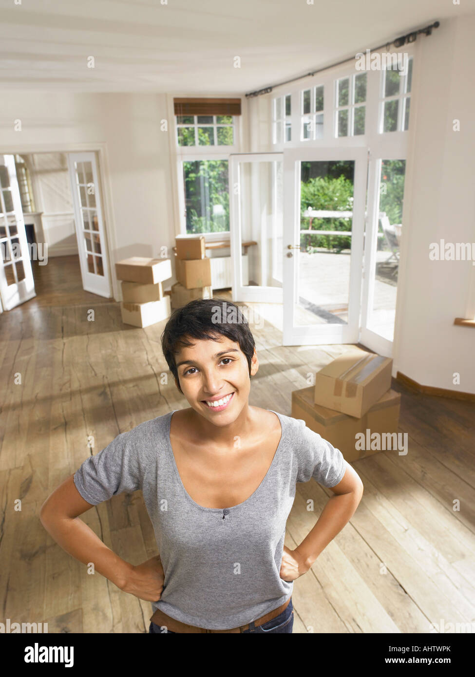 Portrait of a smiling woman moving in empty house  Boxes in