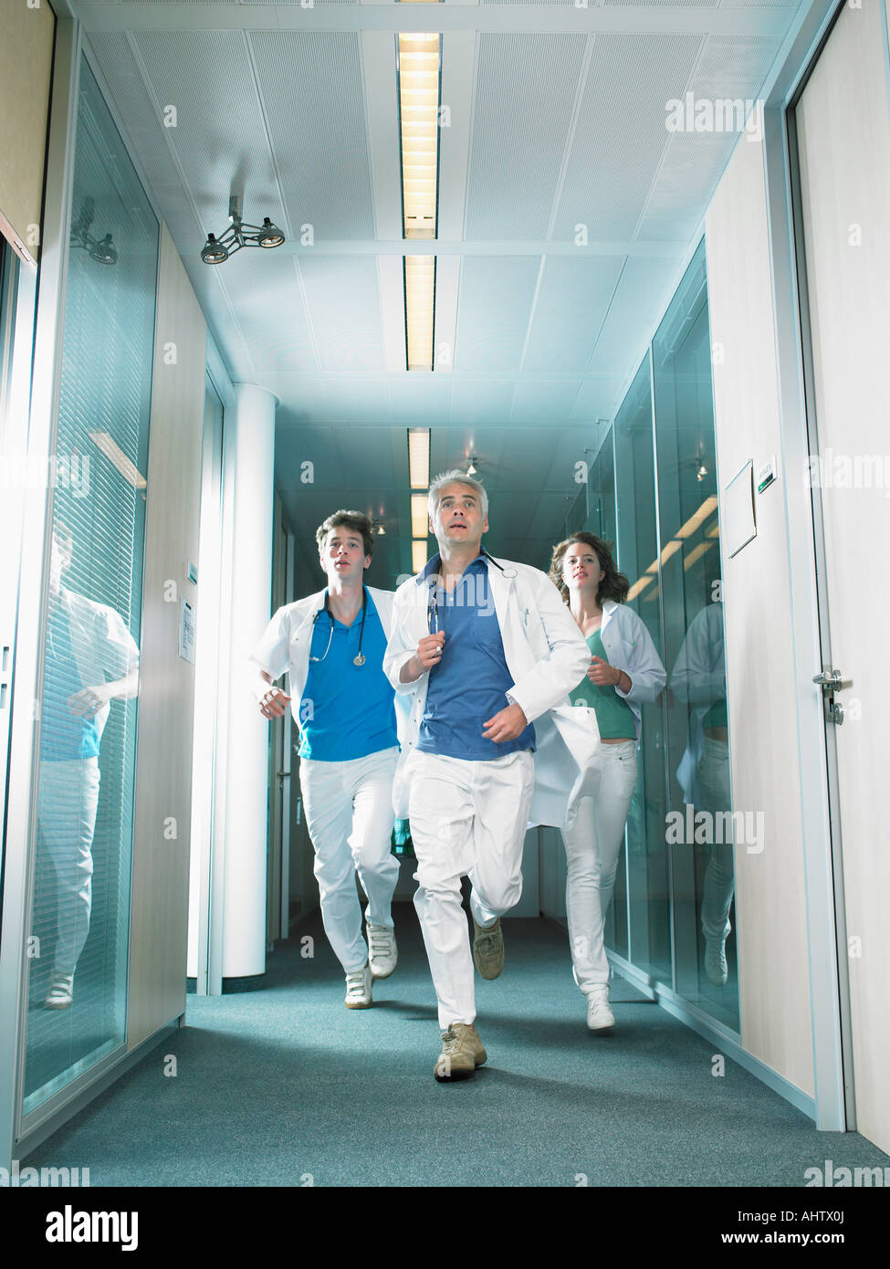 Three doctors running in a lobby of a hospital. - Stock Image