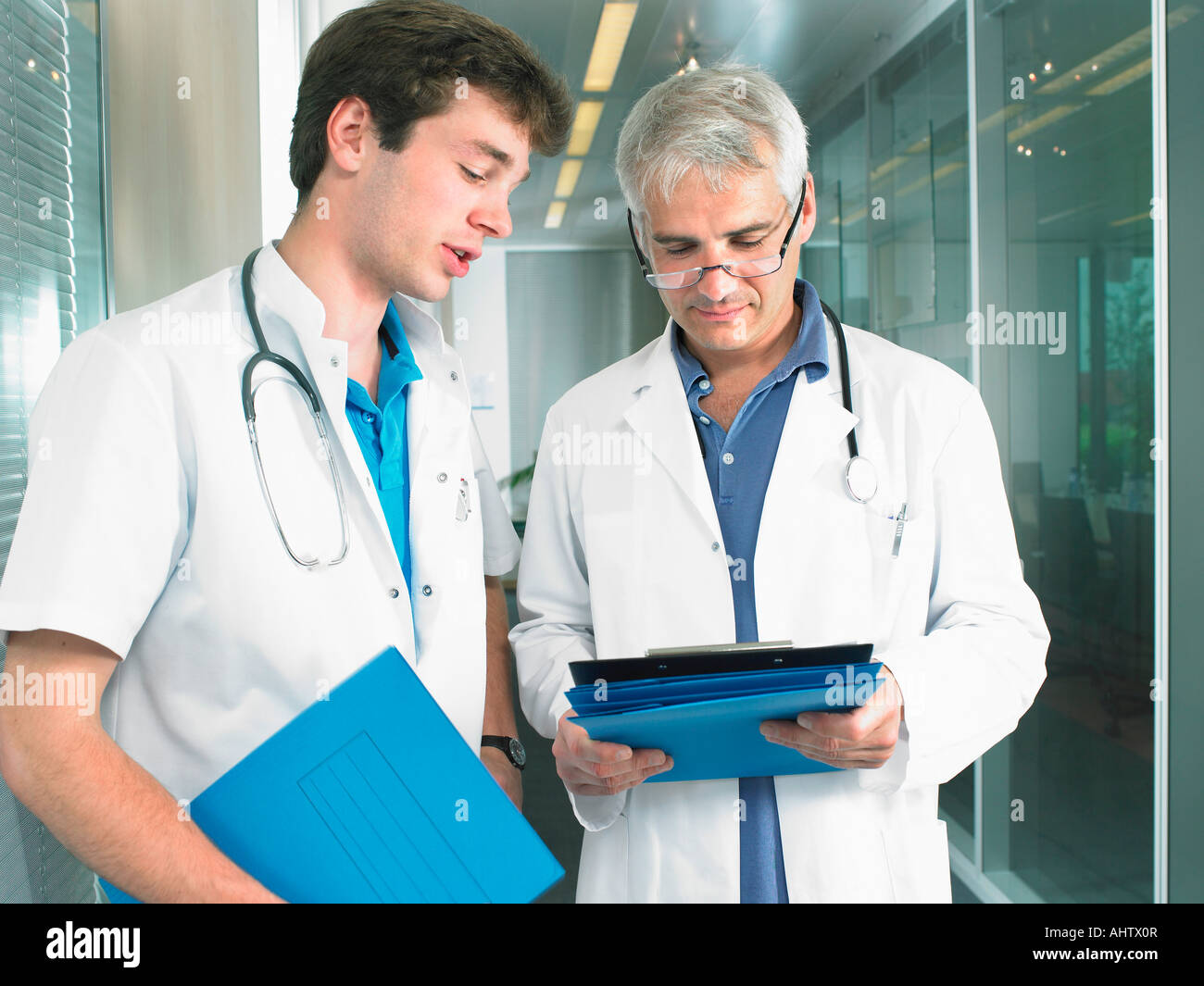 Mature doctor and young doctor in discussion in a lobby of a hospital. - Stock Image