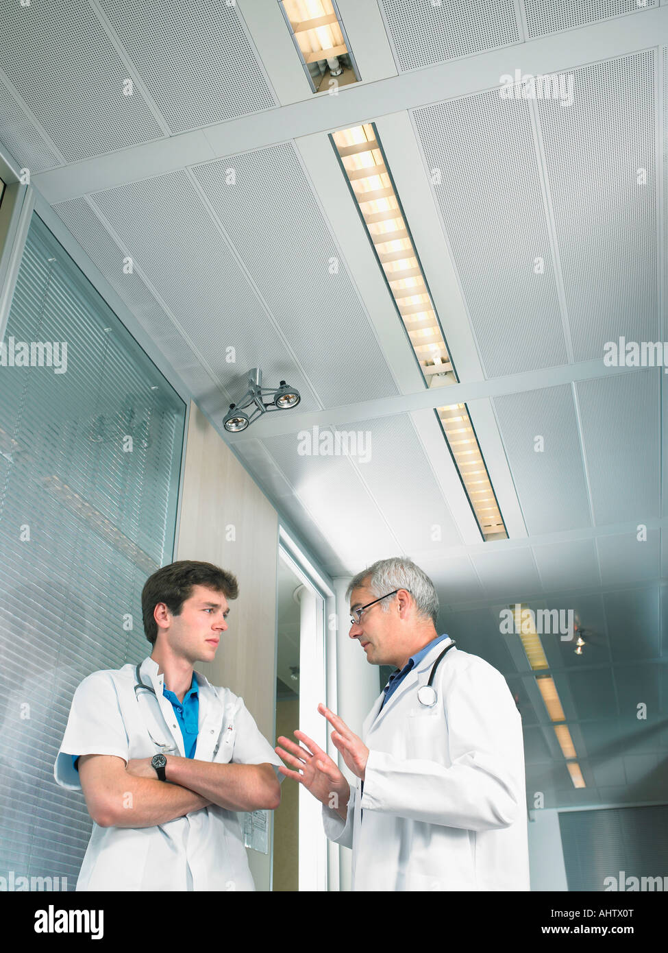 Mature doctor and young doctor in discussion in a lobby of a hospital low angle. - Stock Image