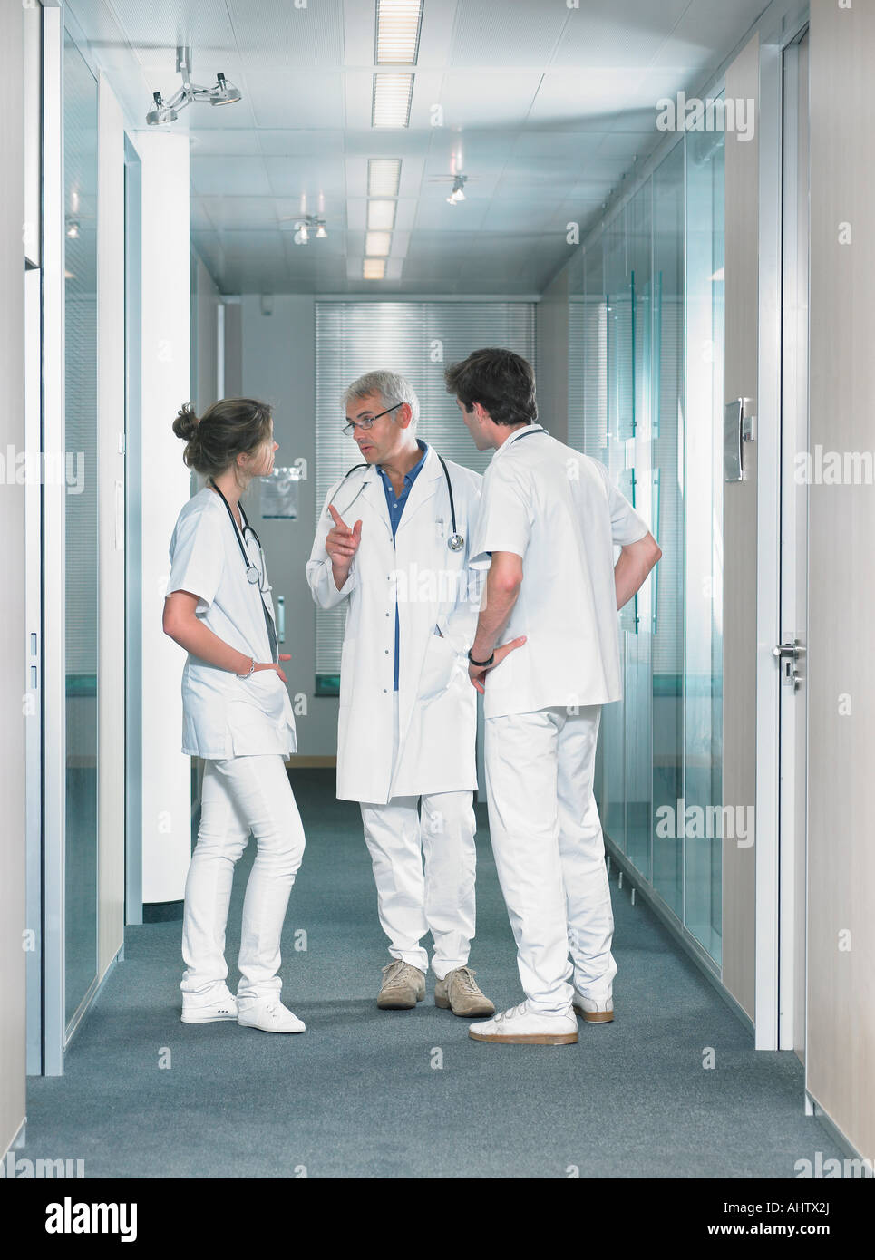 Three doctors in discussion in hospital lobby. - Stock Image