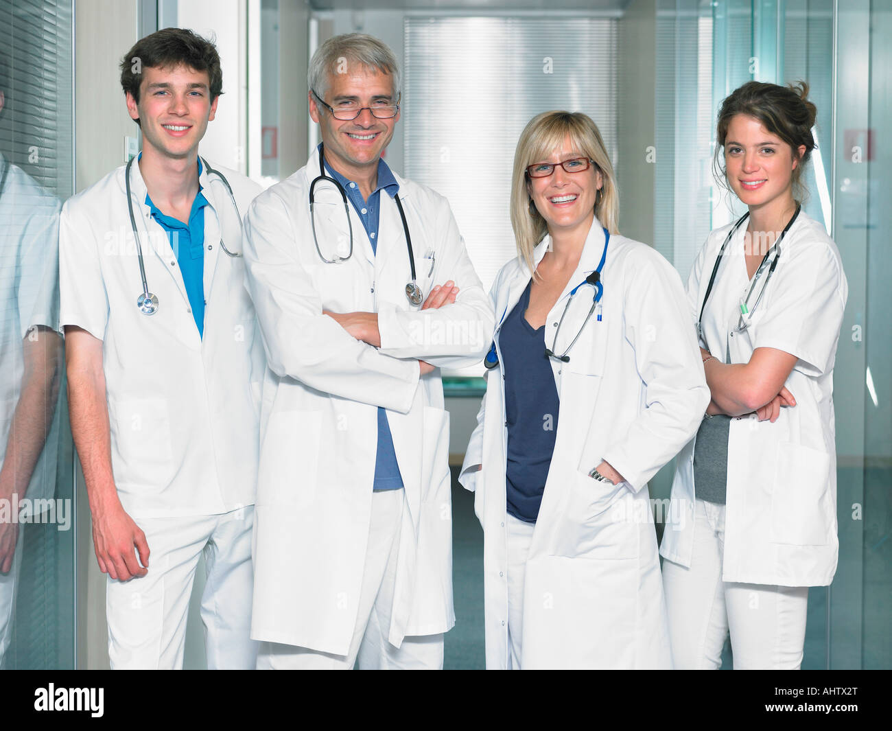 Group shot of four doctors in hospital lobby. - Stock Image