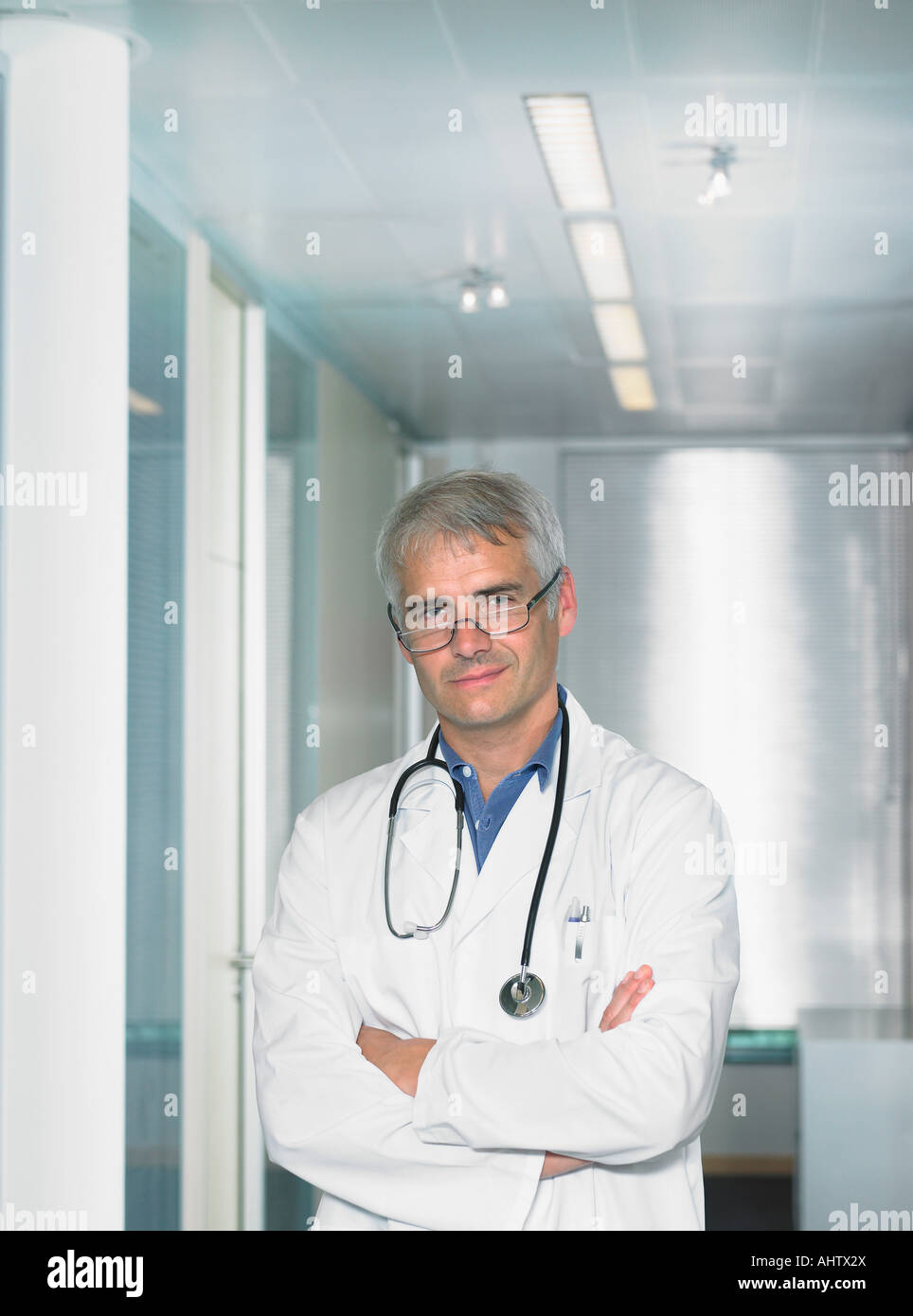 Portrait of mature male doctor in a lobby of a hospital. - Stock Image