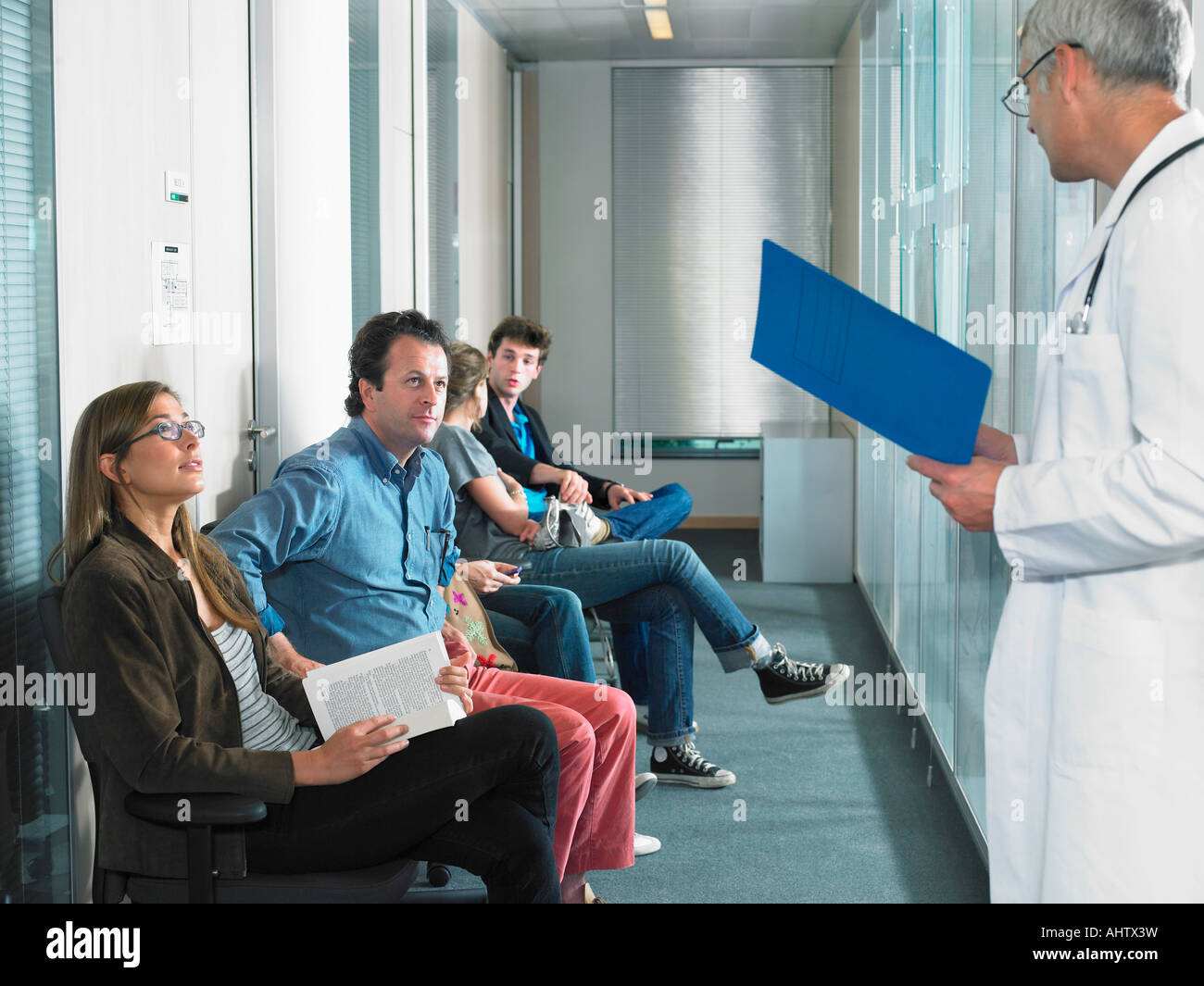 Male doctor calling for patients in hospital waiting room. - Stock Image