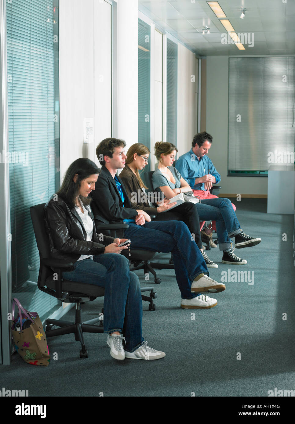 Patients sitting in waiting room of a hospital. - Stock Image