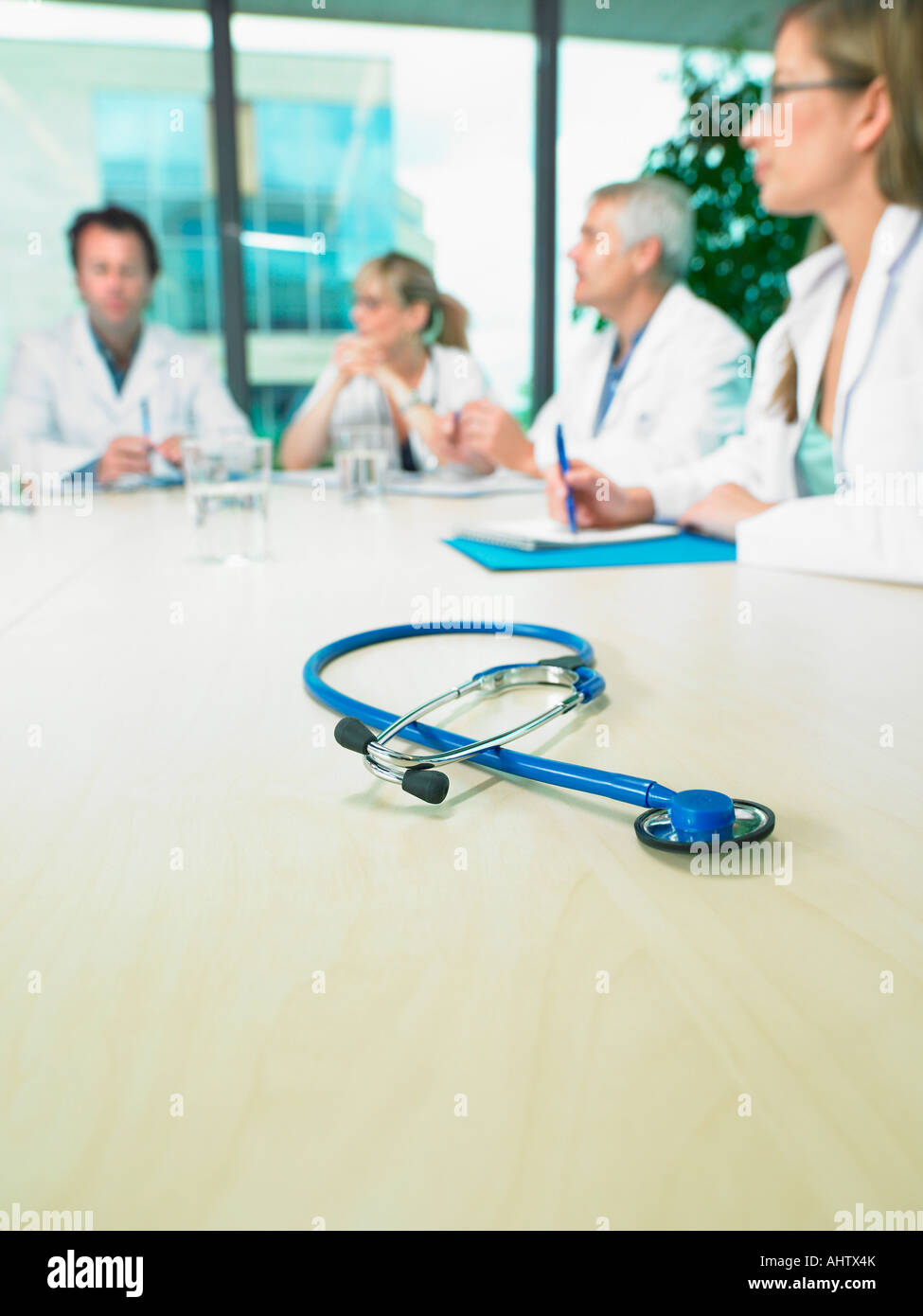 Business meeting of a group of doctors in a conference room around a table. Close up on stethoscope. - Stock Image