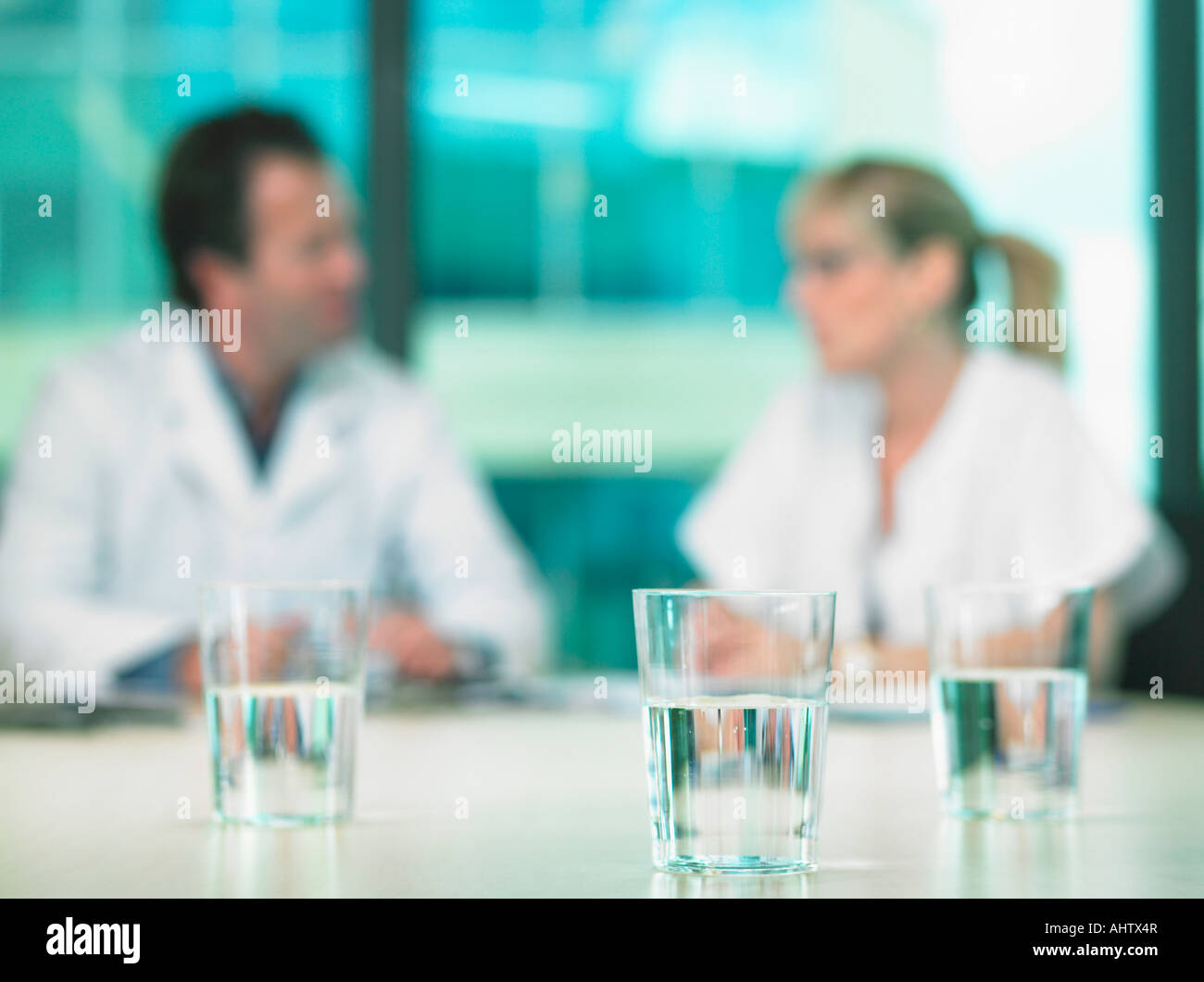 Two doctors in a business meeting. Out of focus. Close up on glasses of water in foreground. - Stock Image