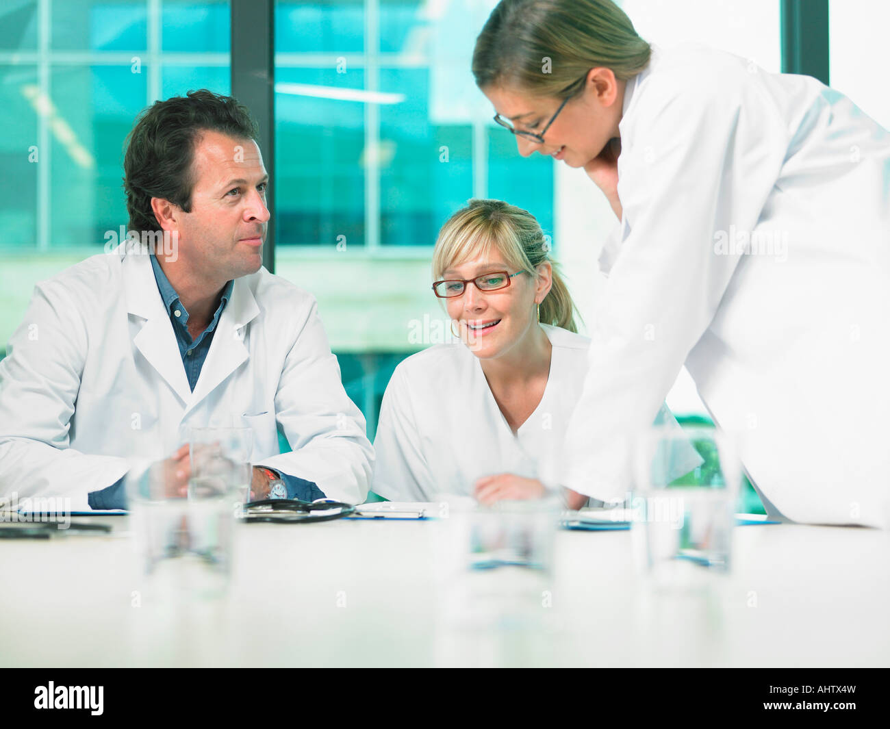 Three doctors smiling and talking in a meeting. - Stock Image