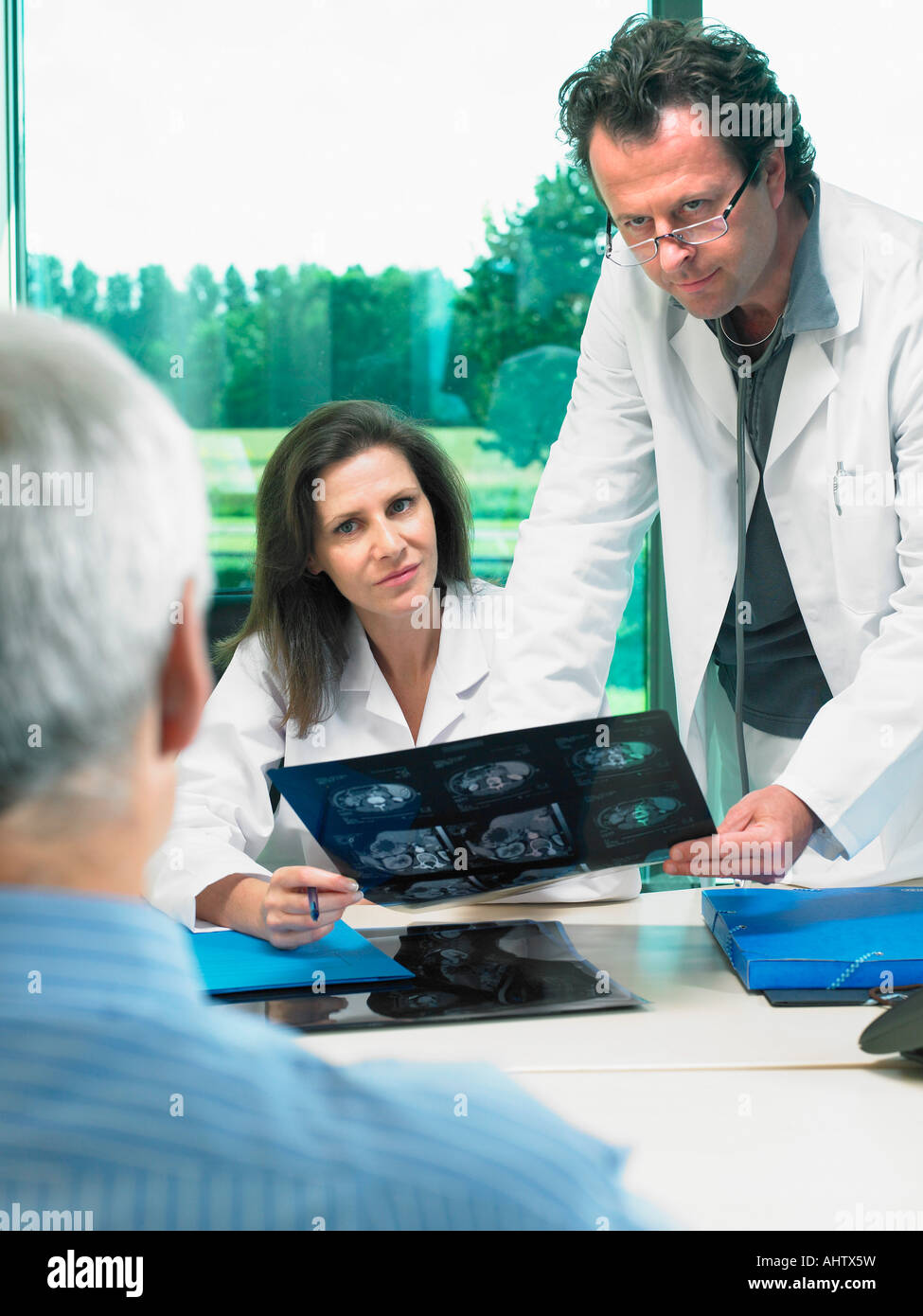 Two doctors in discussion with mature male patient. - Stock Image