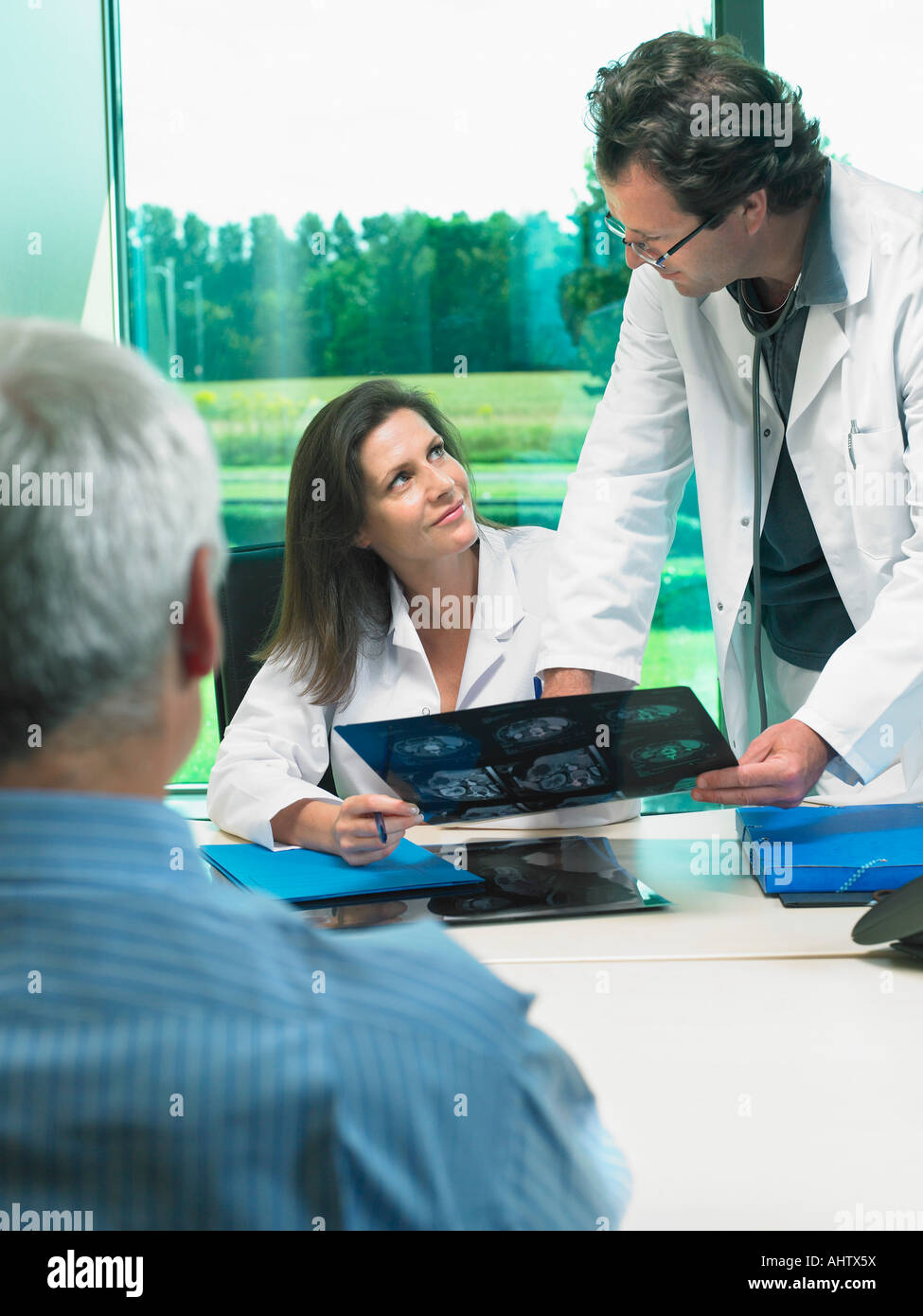 Two doctors discussing x-rays with mature patient. - Stock Image