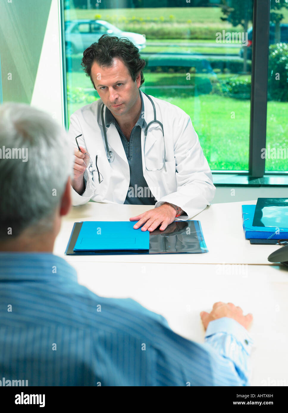 Male doctor at his desk talking with mature male patient. - Stock Image