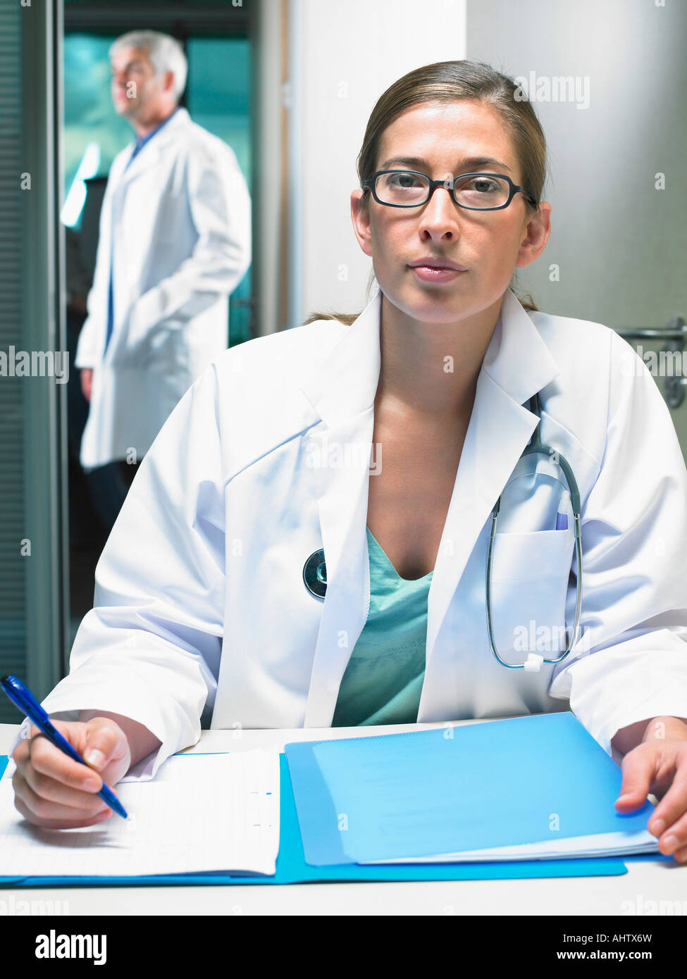 Portrait of female doctor at her desk with male doctor in background. - Stock Image