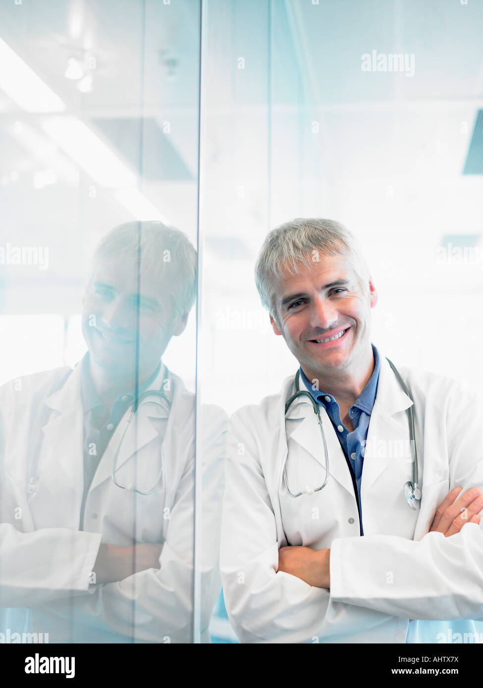 Smiling doctor leaning on wall in hospital lobby. - Stock Image