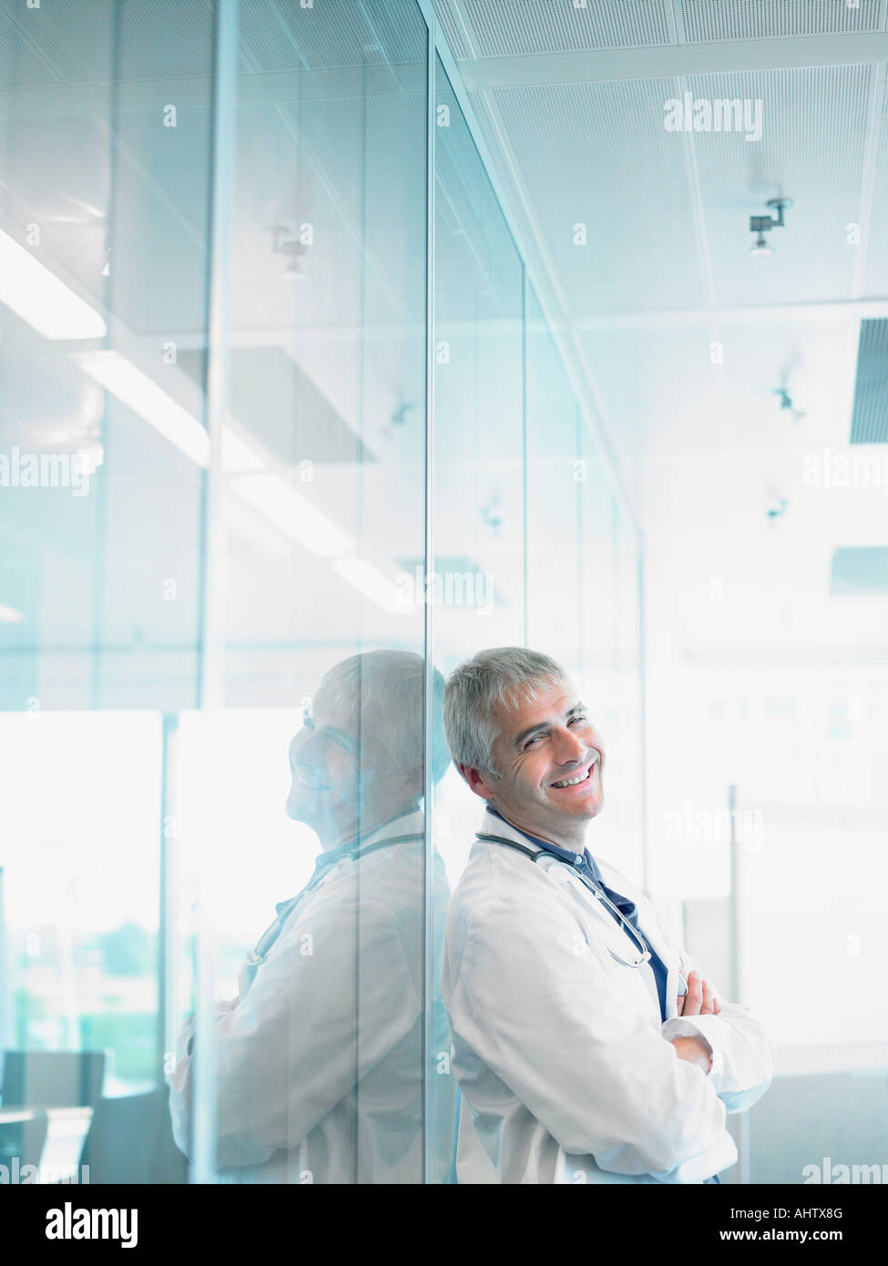 Smiling male doctor leaning on glass wall in hospital lobby. - Stock Image