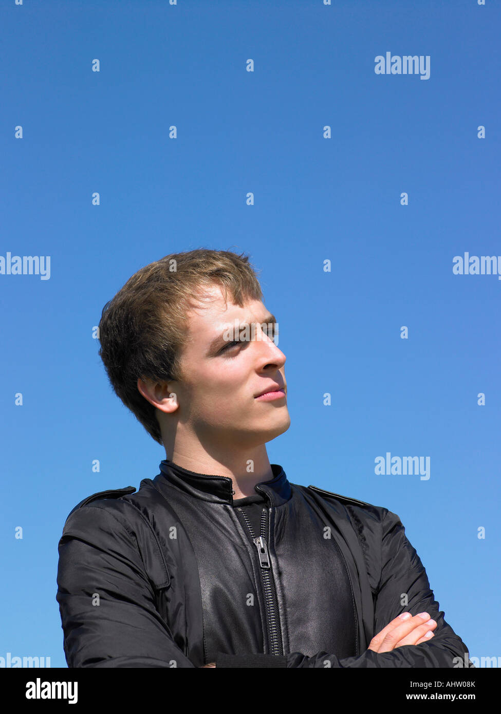 Young man outdoors looking out at something. - Stock Image