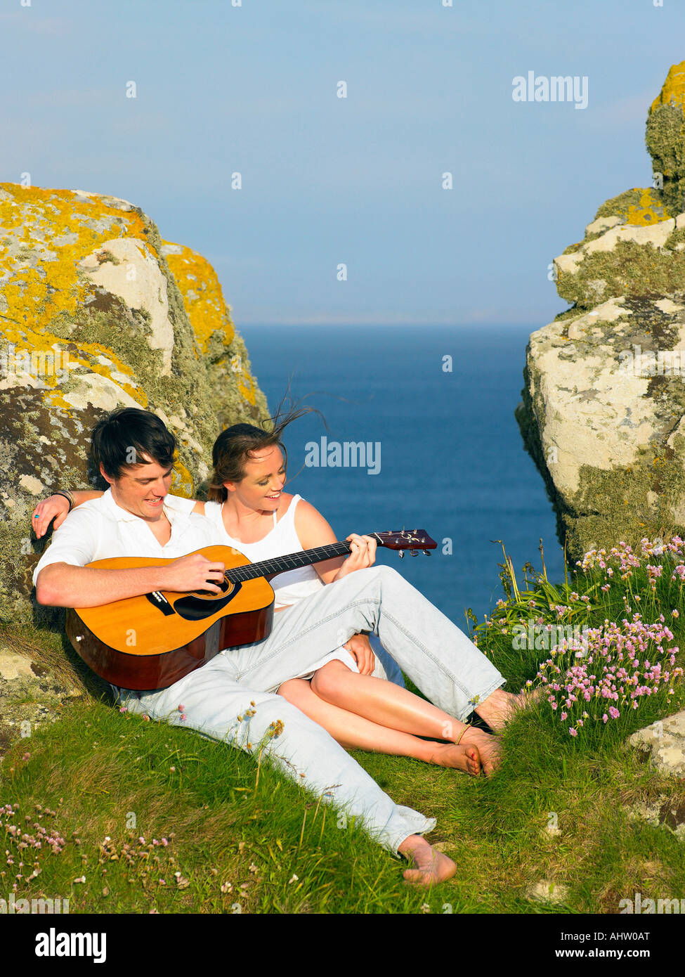 Young couple on a cliff playing guitar. - Stock Image