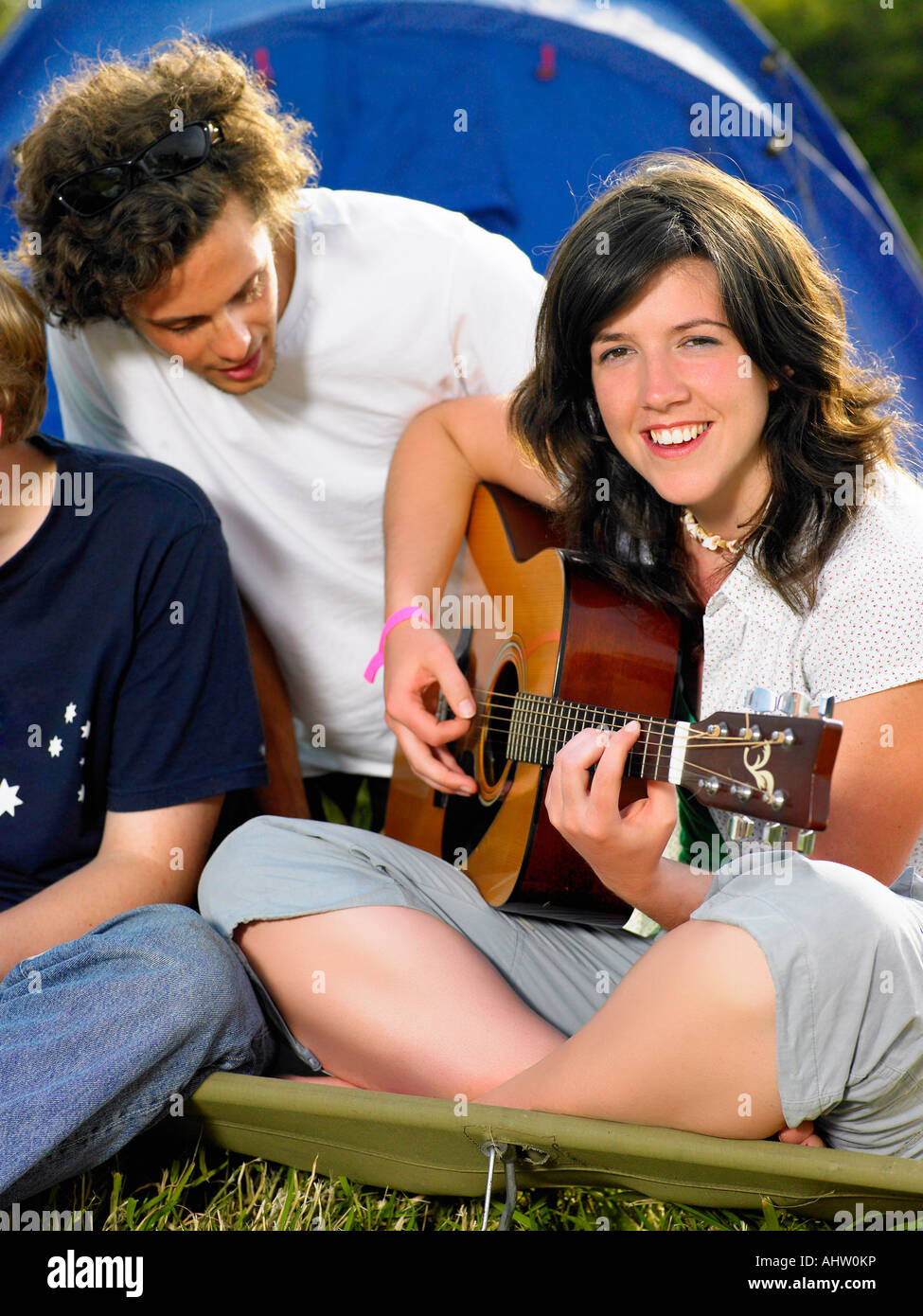 Girl playing guitar while male looks over - Stock Image