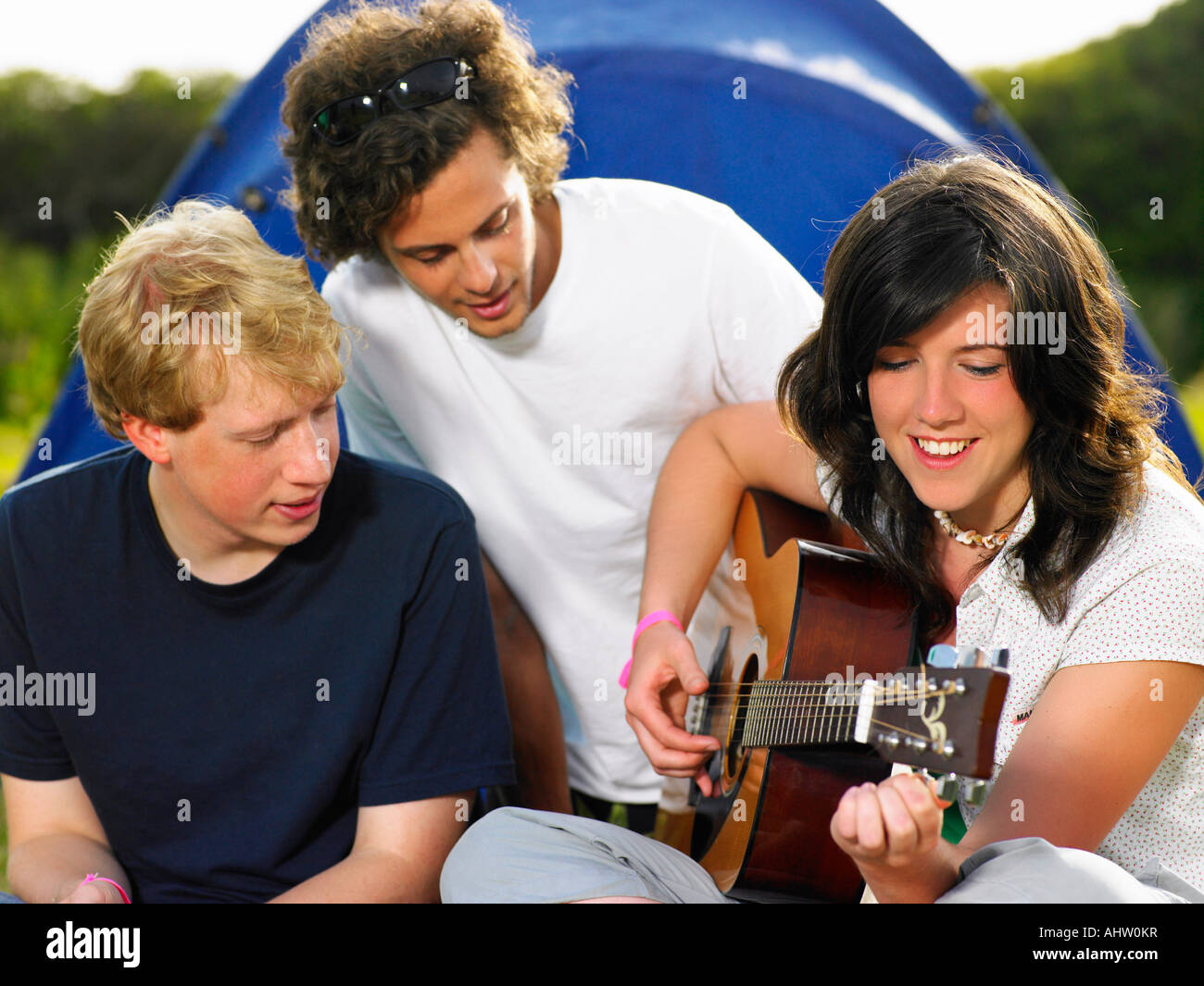 Two young men watching girl playing guitar - Stock Image