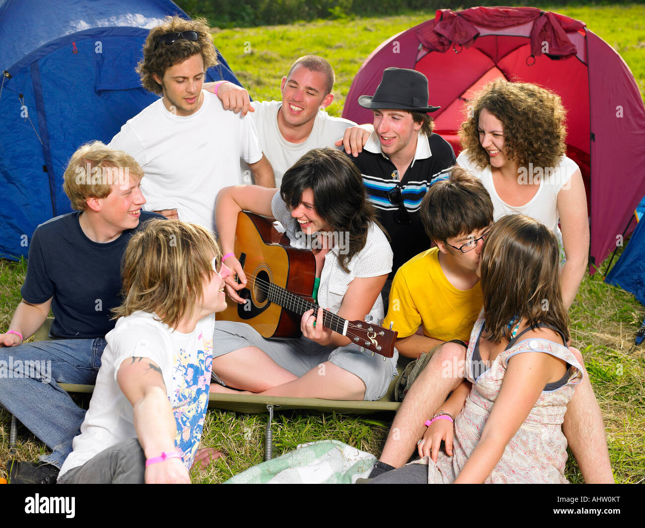Group outside tent one girl playing a guitar - Stock Image